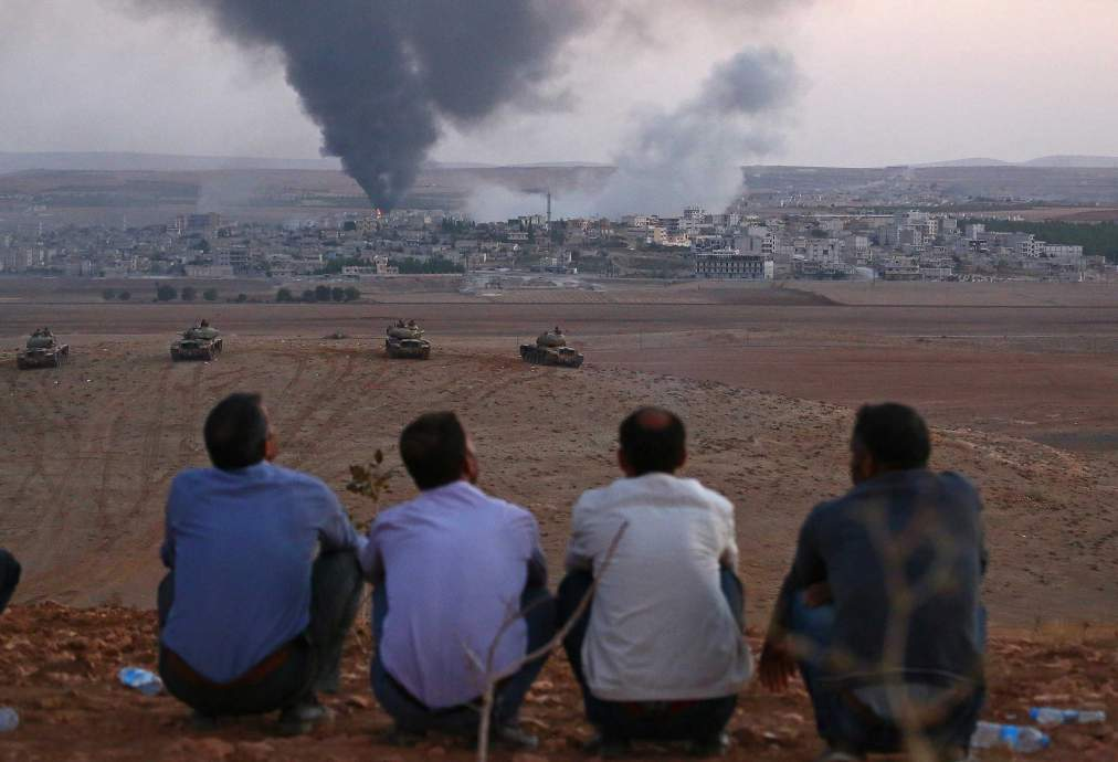 SANLIURFA, TURKEY - OCTOBER 09: Turkish local residents watch the smoke rising from Syria's Ayn al-Arab city (Kobani) after the shelling at the clashes between the Islamic State of Iraq and the Levant (ISIL) and Kurdish armed groups in Ayn al-Arab city on October 9, 2014. (Photo by Emin Menguarslan/Anadolu Agency/Getty Images)